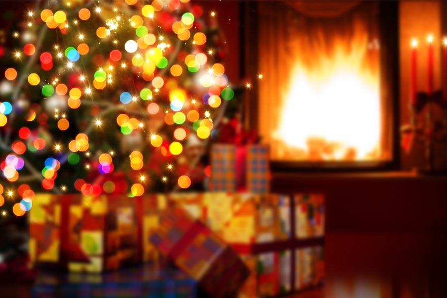 Luces de Navidad en interior de una cal con chimenea encendida de fondo